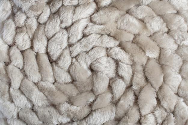 Spiralny wzór dzianiny z naturalnego futra owczego.