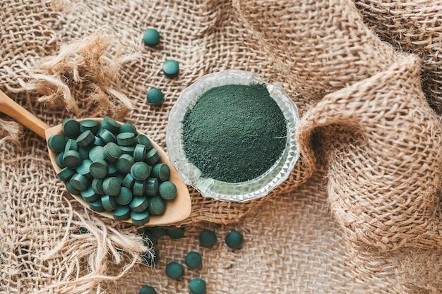Spirulina chlorella tabletki na łyżeczce, proszek w szklanej misce. super pokarm dla zdrowej diety, witaminy, minerały, pierwiastki śladowe dla zdrowia i urody. pożywienie detoksykacyjne.