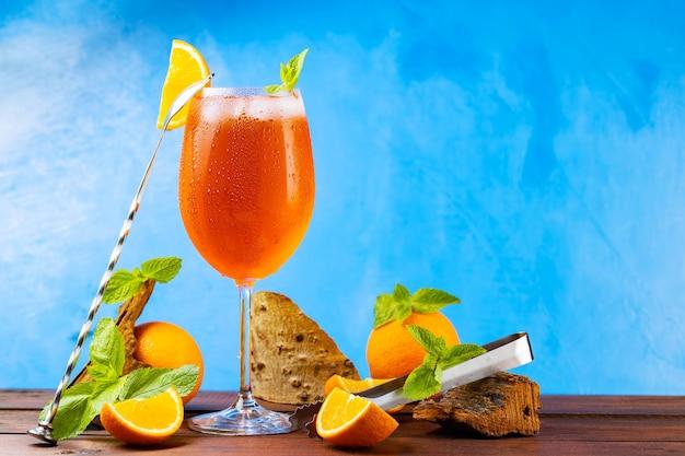 Spitz z aperolem koktajlowym i akcesoria barowe. włoski koktajl aperolowy spritz i pokrojona pomarańcza na niebieskim tle