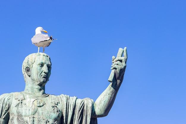Spiżowa statua cesarza cezara nerwy augusta z mewą na głowie jak człowiek robiący selfie