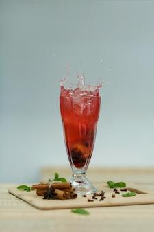Splash cup gorącej witaminy herbaty na drewnianym stole. zimowe gorące napoje sezonowe