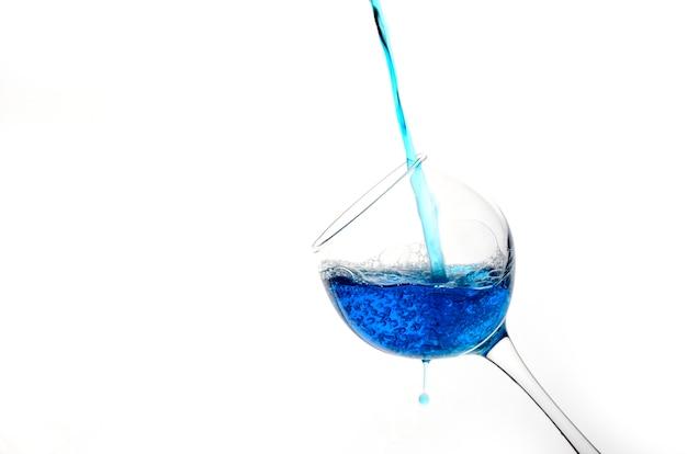Splash modnego niebieskiego wina. koktajl z błękitnym cieczem w szkle z kopii przestrzenią dla teksta.