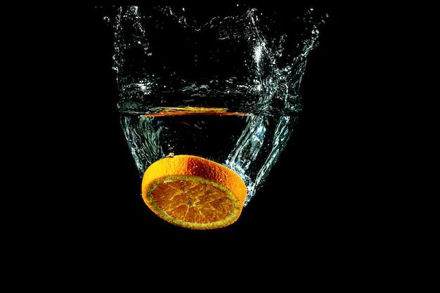 Splash pomarańczowy plasterek pod wodą z czarnym tłem