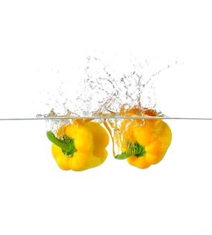 Splash świeżej żółtej papryki w wodzie