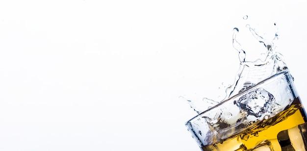Splash whisky z kostkami lodu. koncepcja napojów alkoholowych z lodem, whisky lub brandy, sokiem jabłkowym i napojami chłodzącymi.