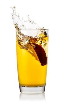 Splash z plasterka jabłka w wysokiej szklance soku jabłkowego