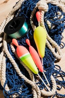 Spławiki i kołowrotek wędkarski na niebieskiej sieci rybackiej