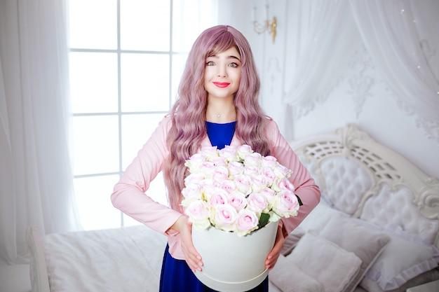 Splendoru uśmiechnięta piękna kobieta z długim lilym włosy trzyma białe pudełko z kwiatami podczas gdy stojący w białej sypialni.