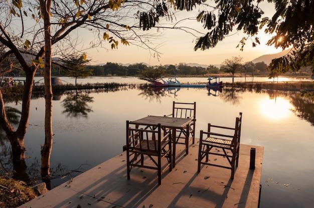 Splot bambusowy stół i krzesła z widokiem na jezioro na nabrzeżu o zachodzie słońca