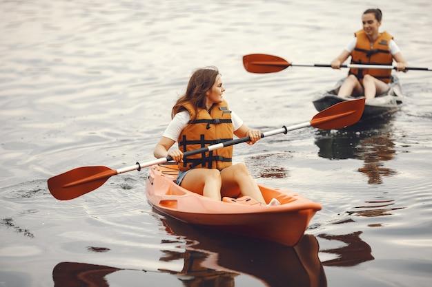 Spływ kajakowy. kobieta w kajaku. dziewczęta wiosłujące w wodzie.