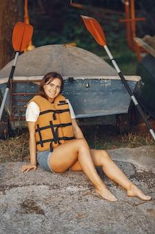 Spływ kajakowy. kobieta w kajaku. dziewczyna siedzi na piasku.
