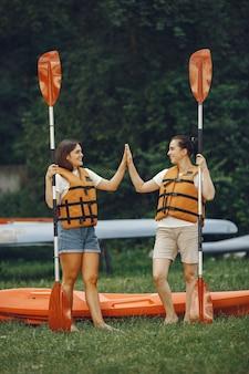 Spływ kajakowy. kobieta w kajaku. dziewczyny przygotowują się do spływu po jeziorze.