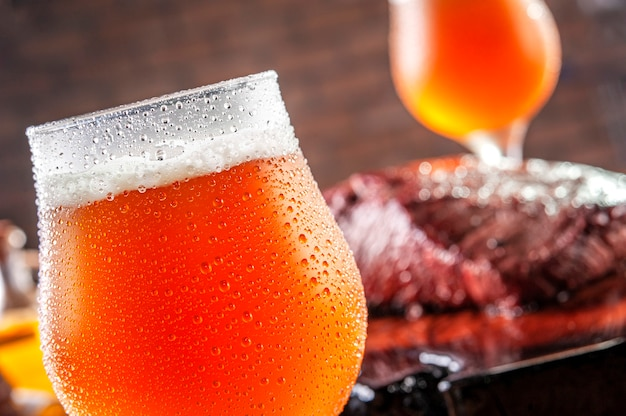 Spocony zimne tulipany szklanki piwa z beczki ale z grillowanym stek denver na drewnianej desce do krojenia - zbliżenie.