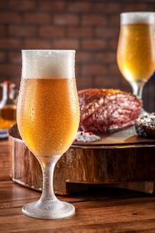 Spocony zimny tulipa szklankę piwa z grillowanym pokrojonym w plasterki stek rump na drewnianą deskę do krojenia (brazylijska picanha).