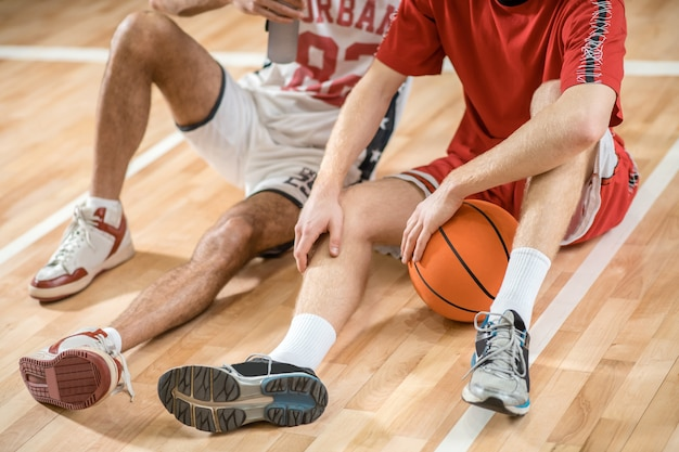 Spoczynkowy. mężczyźni w strojach sportowych odpoczywają po meczu koszykówki i rozmawiają