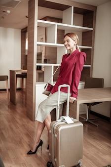 Spódnica i kurtka. promieniejący podekscytowany bizneswoman nosi długą spódnicę i czerwoną kurtkę przyjeżdża do hotelu