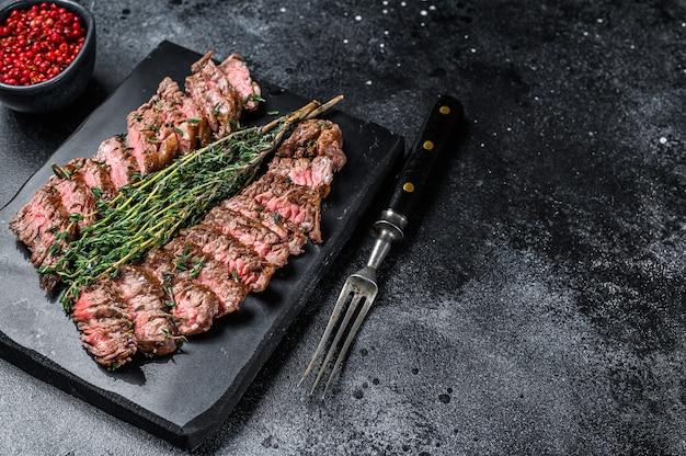 Spódnica maczeta mięso z grilla stek wołowy. czarne tło. widok z góry. skopiuj miejsce.