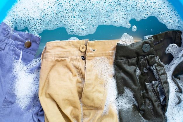 Spodnie moczy się w wodzie rozpuszczającej detergent w proszku