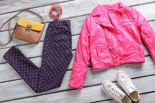 Spodnie w kropki i różowa kurtka. ciemnogranatowe spodnie i torebka. odzież damska na szarej półce. czas się przebrać.