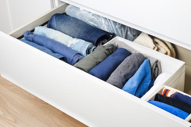 Spodnie złożone zgodnie z metodą marie kondo. pionowe przechowywanie ubrań w komodzie. organizacja przechowywania. porządek i czystość. kwarantanna, izolacja, prace domowe. precyzja.