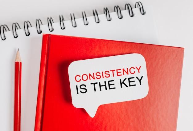 Spójność tekstu jest kluczem na białej naklejce na czerwonym notatniku z tłem biurowym. mieszkanie leżało na koncepcji biznesu, finansów i rozwoju