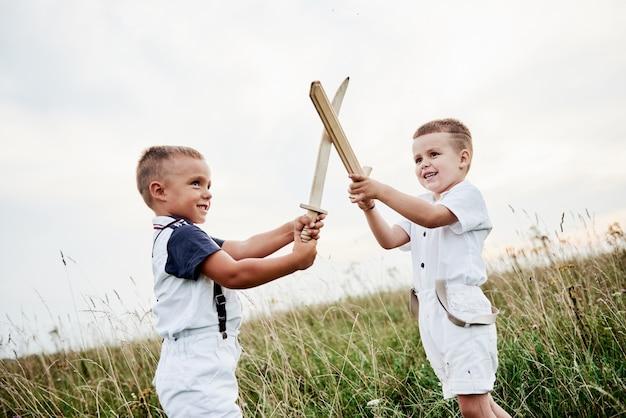 Spójrz, jesteśmy uchwyceni przez kamerę. dwoje dzieci, bawiąc się drewnianymi mieczami w polu.