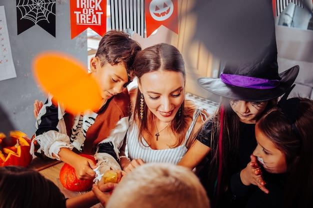 Spójrz na dynie. widok z góry śmieszne słodkie dzieci w garniturach na halloween, patrząc na dynie ze swoim nauczycielem