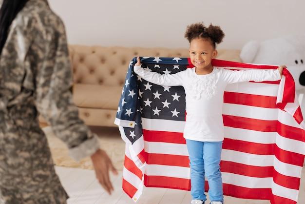 Spójrz na mnie. charyzmatyczne, ładne małe dziecko spotyka swoją matkę w domu, wygląda na szczęśliwe i jest owinięte wielką flagą