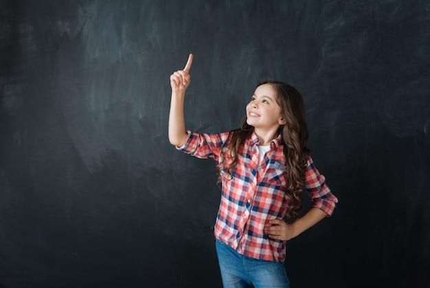 Spójrz na mój genialny pomysł. optymistyczne śmieszne rozbawione dziewczyny stojącej w tablicy i ciesząc się wyimaginowanym rysunkiem, wyrażając jednocześnie pozytywne nastawienie