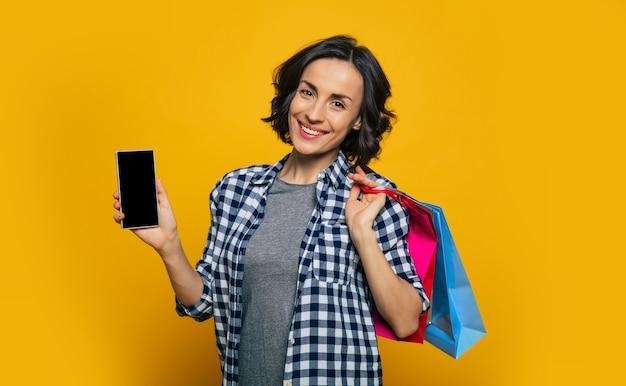 Spójrz na mój telefon. całkiem wesoła dziewczyna, ubrana w biało-czarną kraciastą koszulę, pokazująca swój nowy telefon w prawej ręce i trzymająca zakupy na lewym ramieniu.