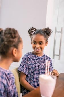 Spójrz na siostrę. mała słodka rozpromieniona uczennica ubrana w fioletową kwadratową sukienkę patrząc na młodszą siostrę