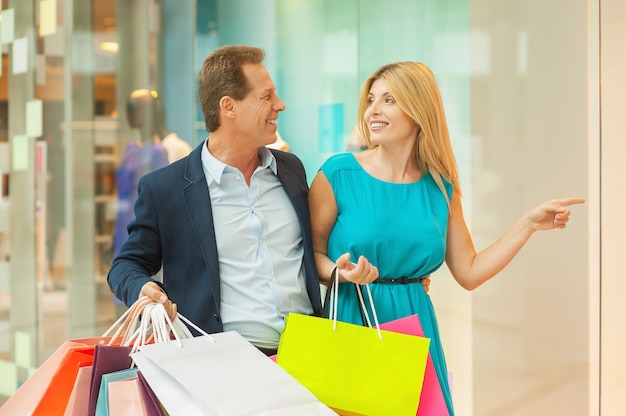 Spójrz na tę sukienkę! piękna dojrzała para robi zakupy razem, podczas gdy kobieta wskazuje i uśmiecha się