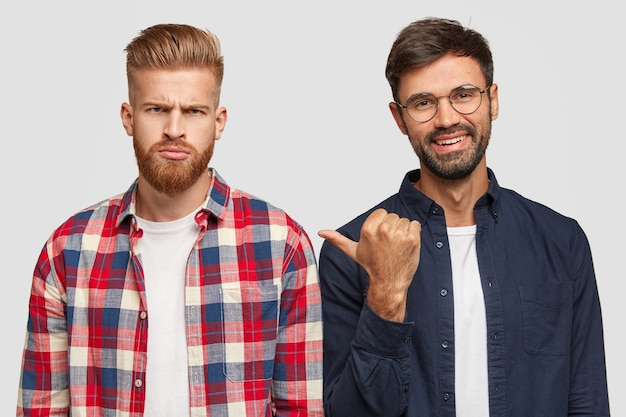 Spójrz na tego faceta. uśmiechnięty nieogolony mężczyzna wskazuje kciukiem na ponurego przyjaciela niezadowolonego z wyników egzaminu