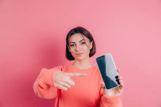 Spójrz na ten telefon komórkowy! zadowolona szczęśliwa kobieta wskazuje palcem wskazującym na pusty ekran, pokazuje nowoczesne urządzenie, szczęśliwe, zaskoczone emocje.