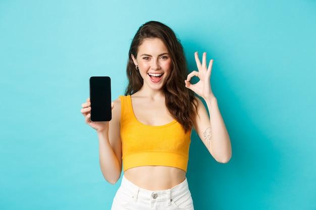 Spójrz na to. przystojna kobieta z promiennym uśmiechem, mrugająca i pokazująca znak porządku z pustym ekranem smartfona, polecająca aplikację, stojąca nad niebieskim tłem.