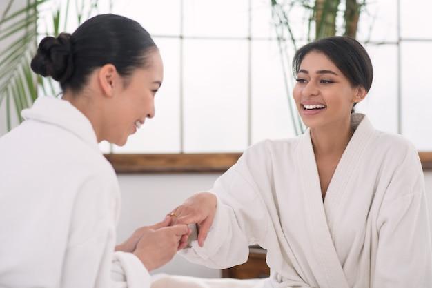 Spójrz na to. szczęśliwa atrakcyjna kobieta, podając jej rękę, pokazując pierścionek zaręczynowy swojemu przyjacielowi