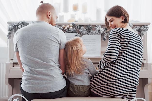 Spójrz od tyłu na matkę ojca i córkę grających na białym pianinie