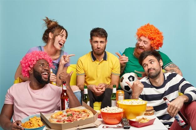 Spójrz, on jest przegrany. szczęśliwi przyjaciele wskazują na nieszczęśliwego faceta, który wspierał inny zespół, który przegrał ten mecz. fani piłki nożnej bawią się, jedzą smaczną pizzę, popcorn, piją napoje alkoholowe, oglądają wielki mecz