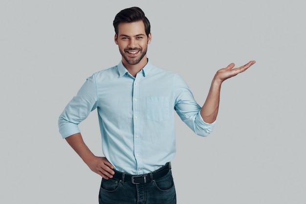 Spójrz! przystojny młody mężczyzna patrzący na kamerę z uśmiechem i wskazujący miejsce na kopię, stojąc na szarym tle