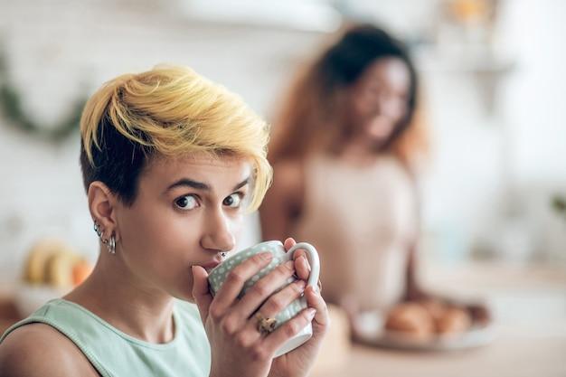Spójrz, pytanie. twarz patrząca z pytającym zainteresowaniem młoda kobieta z krótkimi włosami farbowanymi i kolczykami w uchu pijąca kawę