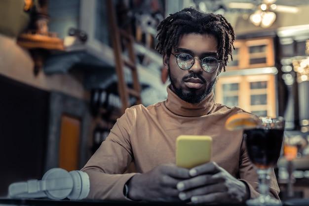 Spójrz. skoncentrowany wolny strzelec siedzący w kawiarni podczas komunikacji online