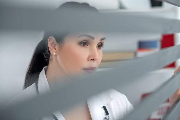 Spójrz, smutku. ciemnowłosa piękna kobieta w białym szlafroku ze smutnym spojrzeniem stojąc i patrząc przez okno w swoim biurze.