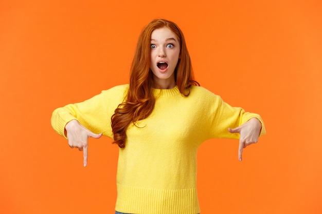 Spójrz szybko. zaskoczona i zafascynowana urocza rudowłosa, rudowłosa studentka w żółtym swetrze