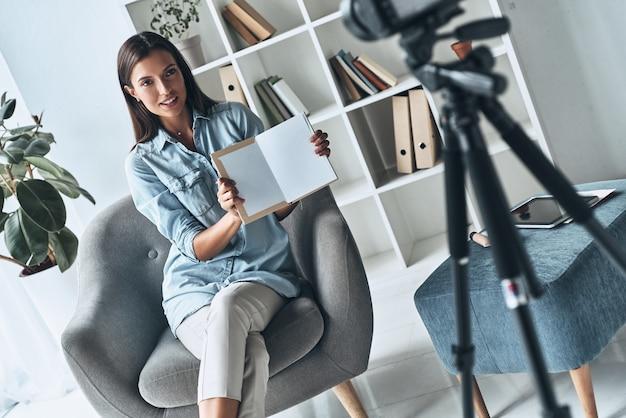 Spójrz tam. atrakcyjna młoda kobieta pokazuje otwartą książkę podczas robienia nowego wideo w pomieszczeniu