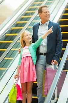 Spójrz tam! wesoły ojciec i córka schodzą w dół ruchomymi schodami, podczas gdy mała dziewczynka trzyma torby z zakupami i wskazuje w bok