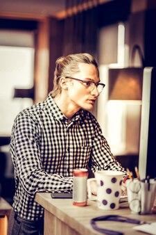 Spójrz. uważny freelancer wpatrujący się w swój komputer podczas tworzenia zadania