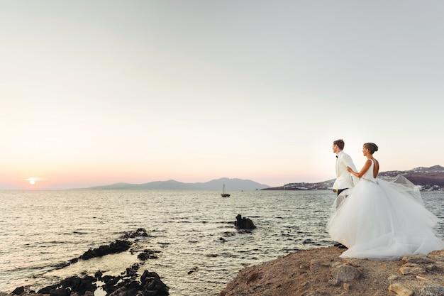 Spójrz z daleka na uroczą parę weselną, obserwując zachód słońca nad morzem