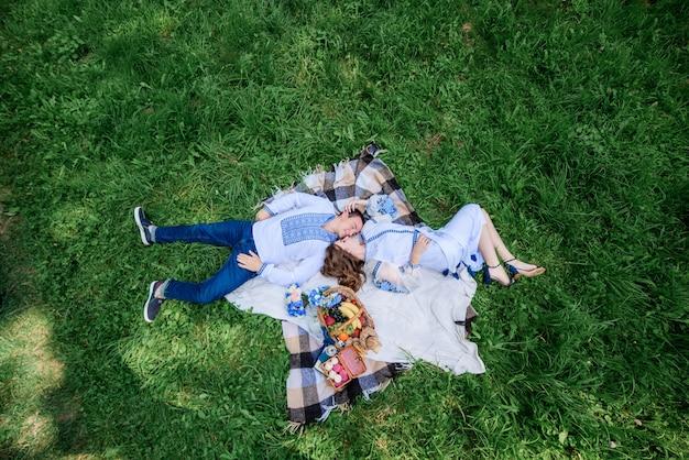 Spójrz z góry na uroczą parę weselną leżącą obok siebie na trawniku
