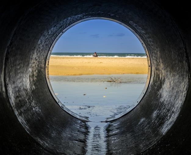 Spójrz z rury patrząc na plażę otoczoną morzem z ludźmi w niej oświetlonymi światłem słonecznym