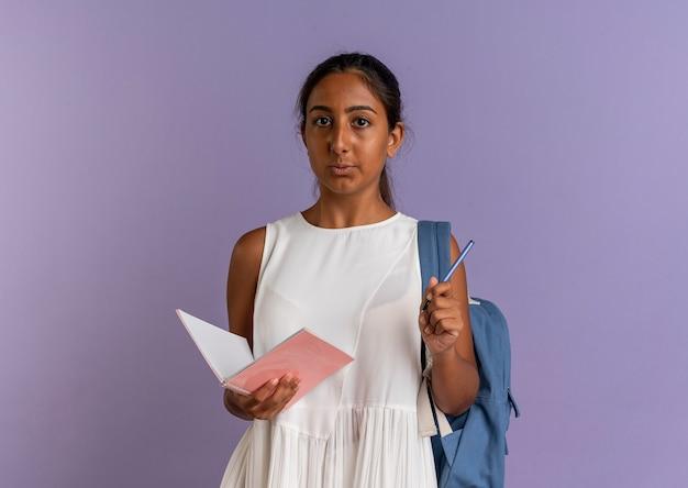 Spojrzenie na aparat fotograficzny młoda uczennica sobie z powrotem torbę trzymając pióro z notatnikiem na fioletowym tle